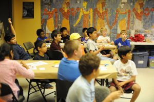 Kids at the museum summer camp listen to a lesson while working on their projects.
