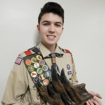 Houston boy scout holds dinosaur fossil while attending Scouts at the Museum.