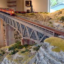 The largest model train in Texas glides along a bridge surrounded by a hand-crafted Texan environment.