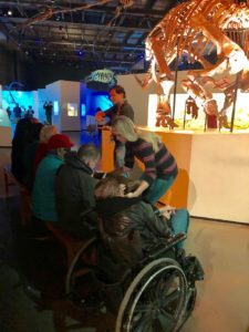 Two museum employees lead a touch tour for people who are blind and low vision in the morian hall of paleontology