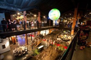 Overhead shot of a cocktail-style corporate event showing the t. rex dinosaur skeleton and science of a sphere.