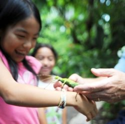 Young student holding an insect and smiling as a part of our early investigators field trip.