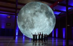 Image shows large moon sculpture with real NASA imagery in front of a group of children with their hands raised.