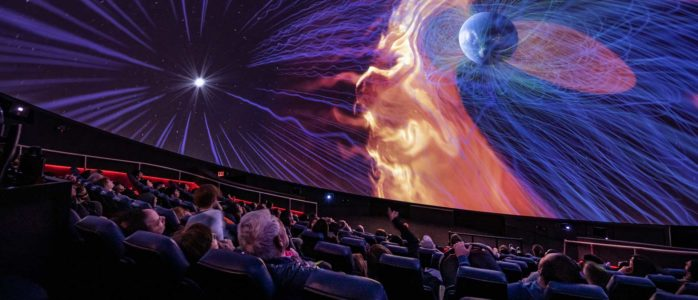 Museum guests watch from seats in the burke baker planetarium as an astronomy show plays on the screen