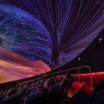 Guests at the museum watch from seats in the burke baker planetarium as an astronomy show plays on the screen.
