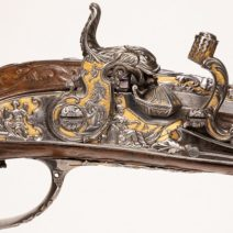 A closeup of the engraving and metal work on an antique firearm from the 16th through 18th centuries