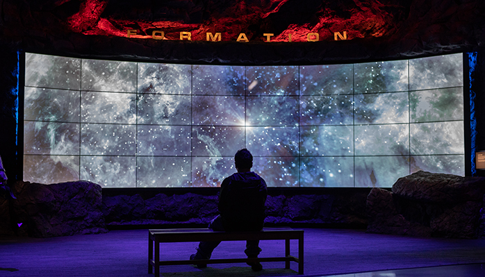 A silhouetted child sits in front of a screen in the wiess energy hall depicting the formation of the galaxy.