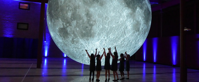 A large moon sculpture commemorating the 50th anniversary of the apollo 11 moon landing hangs above the heads of young students.