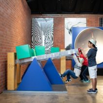 A child plays with a see-saw physics display at a science museum in sugar land, texas.
