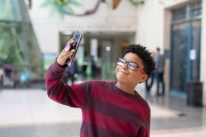 A young guest at the houston museum of natural science uses his cell phone to take a selfie.