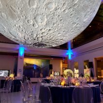 Table settings for an elegant seated dinner party sit beneath moon by luke jerram a large art sculpture