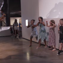 Five kids practice their dinosaur roars during a kid's summer event.
