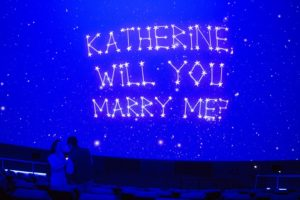 """The image shows a creative proposal at the museum; a newly engaged couple stands in the planetarium under a screen that reads """"Katherine, will you marry me?"""" written in stars."""