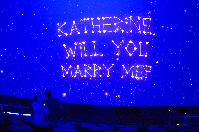"The image shows a creative proposal at the museum; a newly engaged couple stands in the planetarium under a screen that reads ""Katherine, will you marry me?"" written in stars."