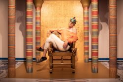 A person sprawls across the a replica ancient Egyptian throne at the Houston Museum of Natural Science.
