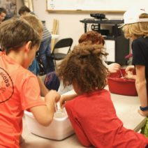 A group of students lean over science experiment during one of our weekday labs.