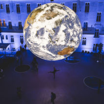 Large Earth sculpture hangs in an event space.
