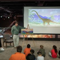 Associate Curator of Paleontology reads his book Big Adventures with Dino Dave to a group of children at the museum.