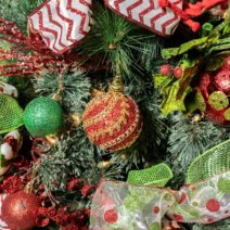 Closeup of a Christmas Tree for sale at Jingle Tree. Image shows red, green and gold ornaments hanging from a green pine tree surrounded by red white and green ribbons and garland.