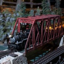 Model 0 train set runs under a Christmas tree in seasonal holiday display Trains Over Texas at the Houston Museum of Natural Science