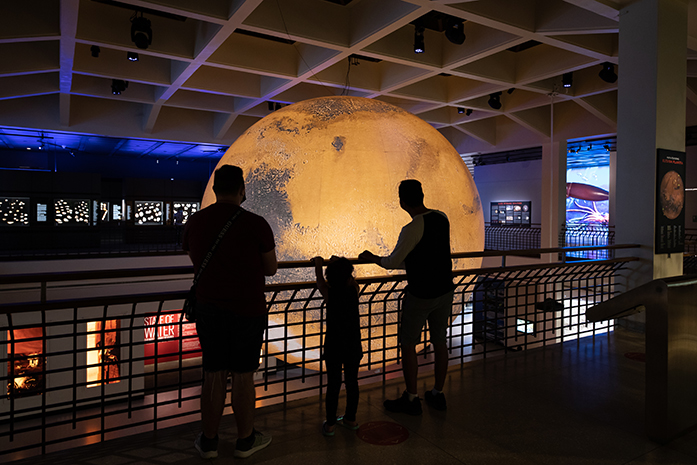 Three museum visitors look over into the Glassell Hall and observe Mars, A sculpture by Luke Jerram.