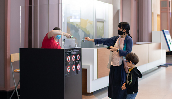Museum guest services greet a group of people while safely socially distancing.