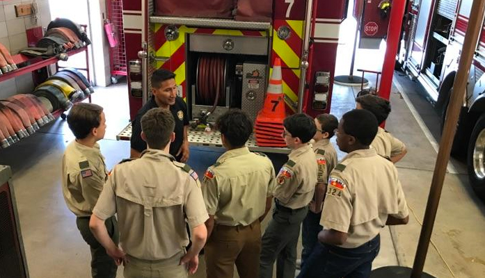 A group of Scouts BSA members are led in instruction at a local fire station.