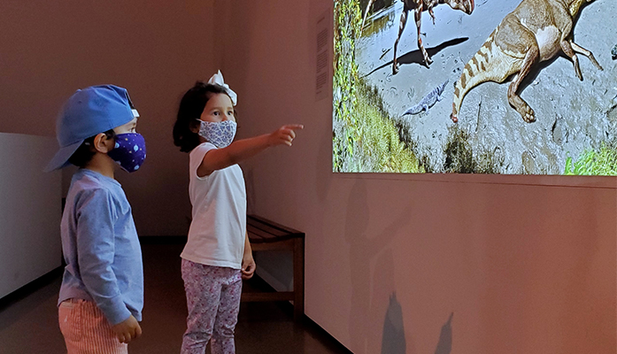 Two kids explore a mural of dinosaurs in the Morian Hall of Paleontology as one points into the jurassic depiction.