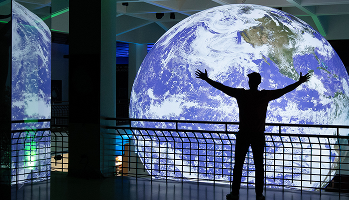 A silhouette stands in front of a large Earth Sculpture, by Luke Jerram, hanging from the ceiling in the heart of the Houston Museum of Natural Science